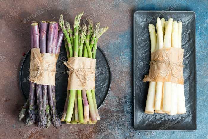 Homegrown fresh natural color organic asparagus spears on a slate plate on a wooden background. Top