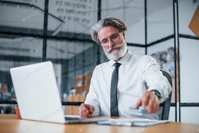 Hombre de negocios maduro con pelo gris y barba en ropa formal sosteniendo dinero en las manos