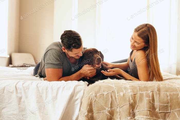 Young couple with their dog on the bed in morning