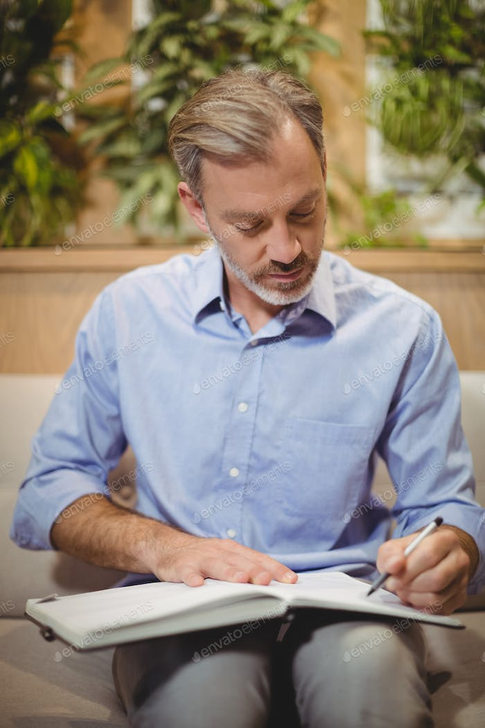 Attentive doctor writing in organizer