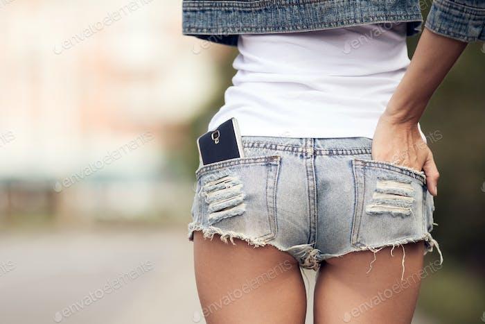 Frau zurück Nahaufnahme. Smartphone In Jeans Kurze Tasche.