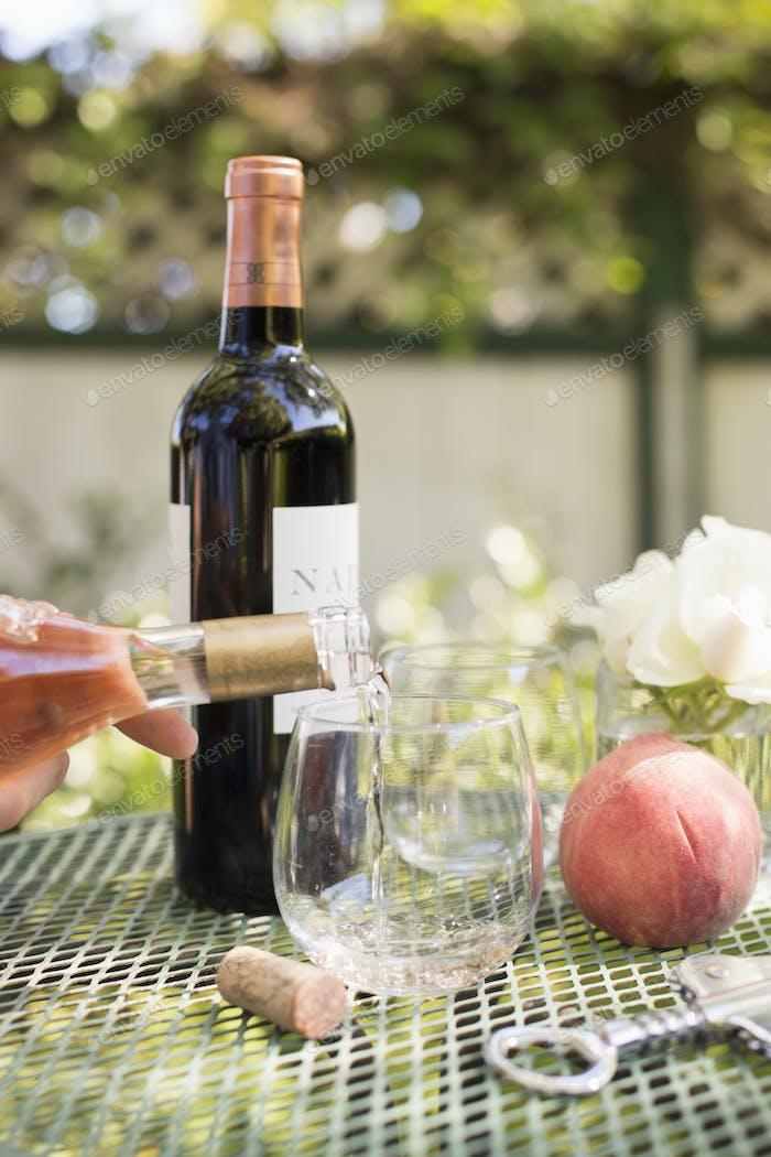Rosenwein wird aus einer Weinflasche in ein Glas gegossen.