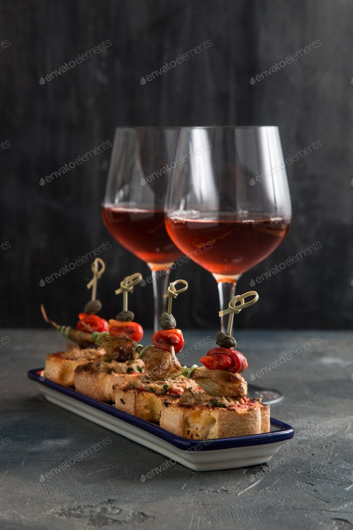 spanish tapa pinxtos with tuna, peper, onion and oregano. Wine on background