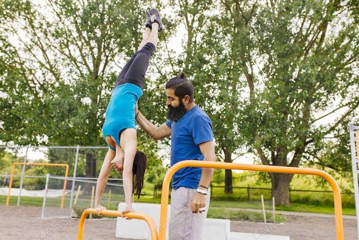 Man helping woman doing handstand