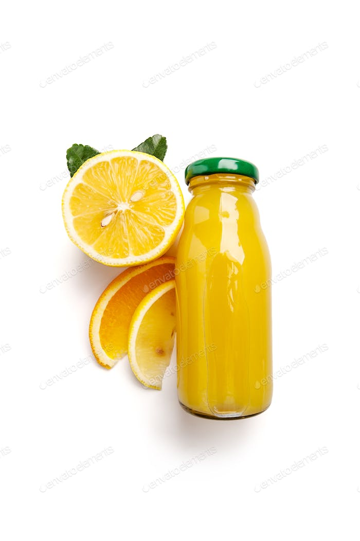 Citrus fresh squeezed juice in a small glass bottle and fresh le