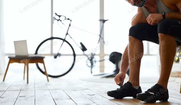 Young man putting on sports shoes at home