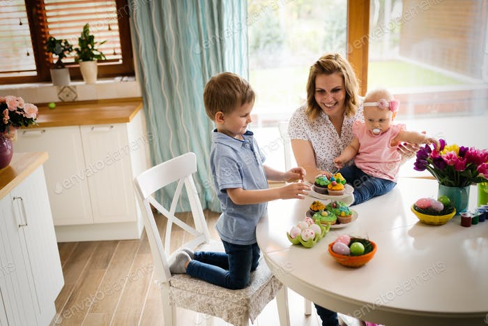 Happy easter. A mother and her kids painting Easter eggs