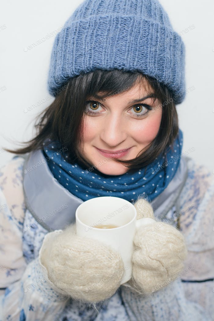 cute woman in winter clothes holding cup with tea on white backg