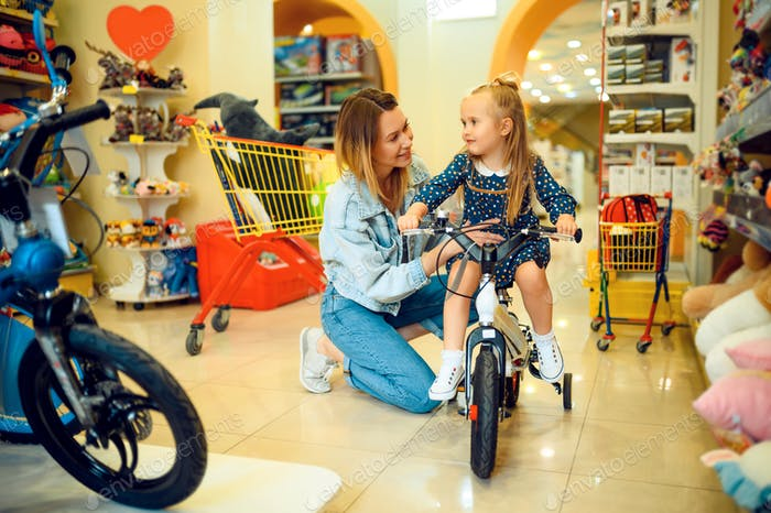 Mom and little girl buying bicycle in kid's store
