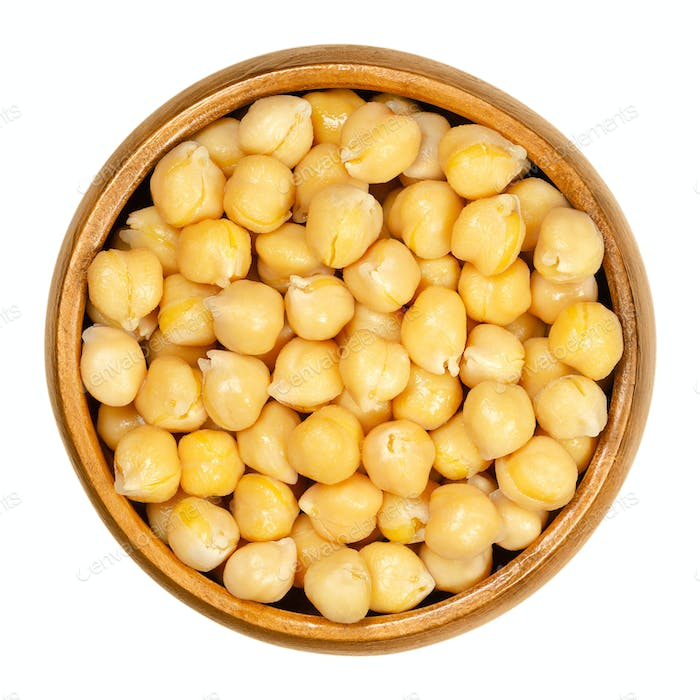 Cooked chickpeas in wooden bowl over white