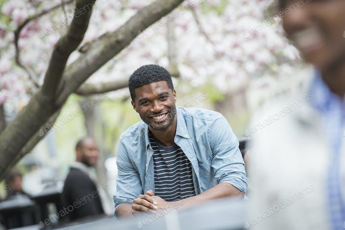 Frühling in der Stadt, Ein Mann sitzt an einem Tisch lächelnd. Eine Frau im Vordergrund.