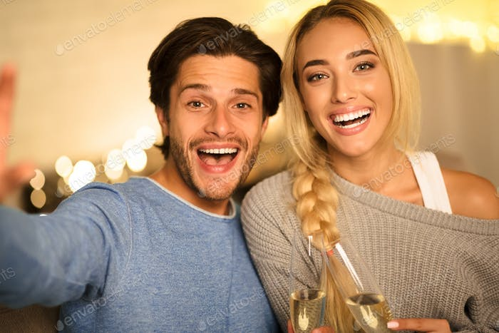 Beautiful couple making selfie and clinking champagne glasses