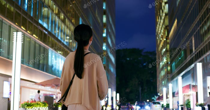 Woman standing in front of the building at night