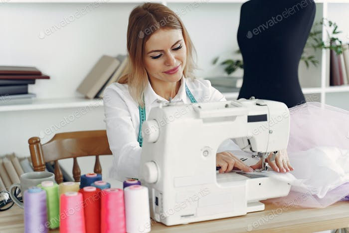 Woman sitting in studio and sew cloth