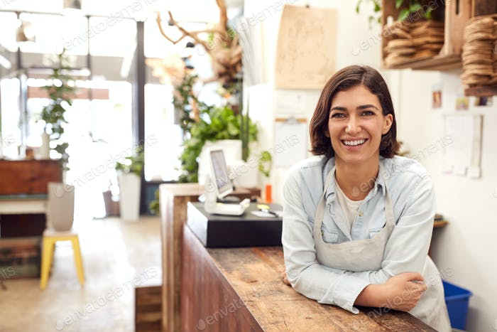 Portrait Of Smiling Female Sales Assistant Standing Behind Sales Desk Of Florists Store