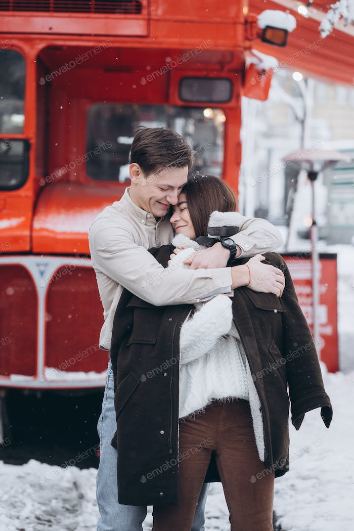 young guy warms his beautiful girl with jacket on a snowy street