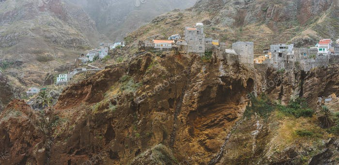 Settlement in the rocky coast of Santo Antao island. Houses nestle into the bluff ridge wall