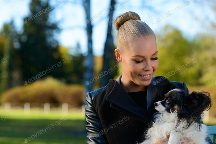 Young happy woman smiling while holding and looking at cute dog in the park