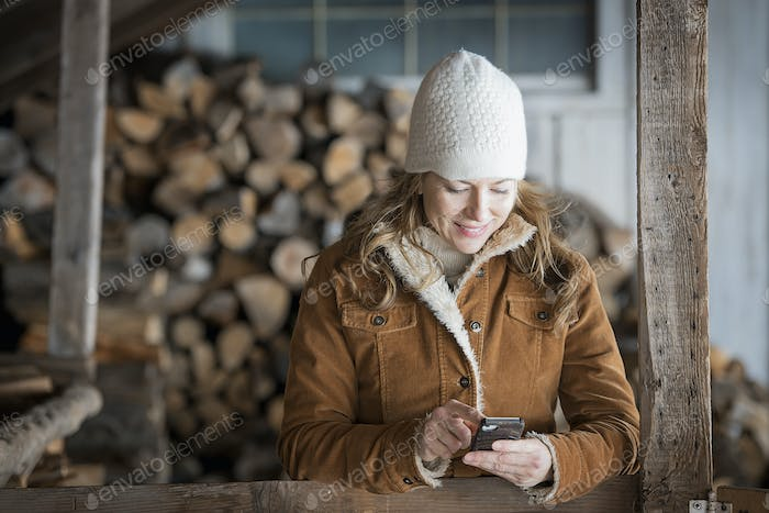 A woman in sheepskin coat and woollen hat using a cell phone outside on a farm.
