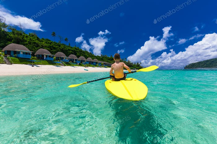 Young shirtless caucasian boy kayaking at tropical sea on a kaya