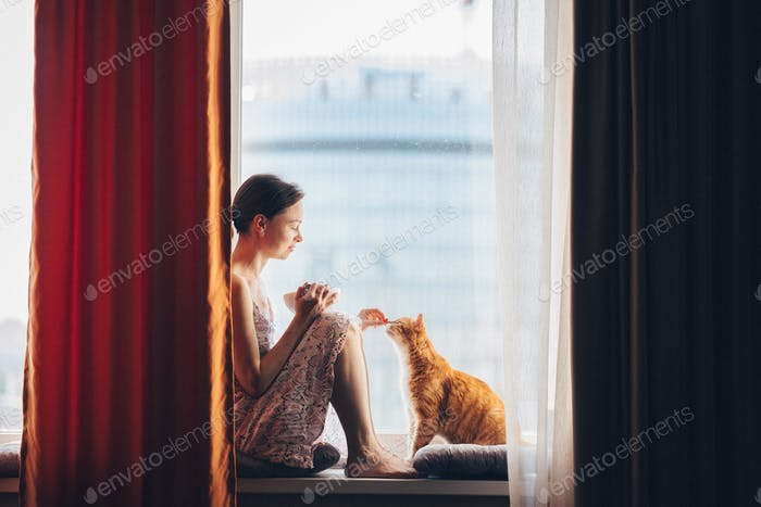 Young girl with a red cat at home
