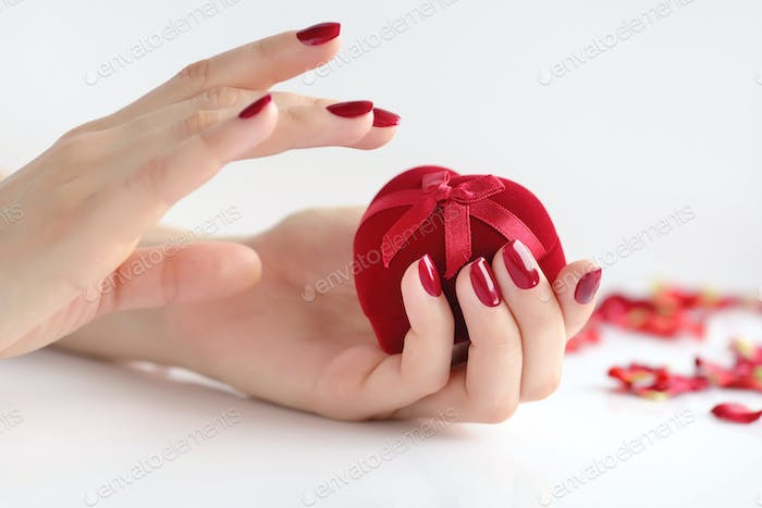 Beautiful female hands with red manicure holding a box of heart-