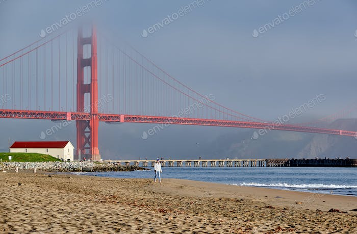 Woman walking on beach near Golden Gate Bridge