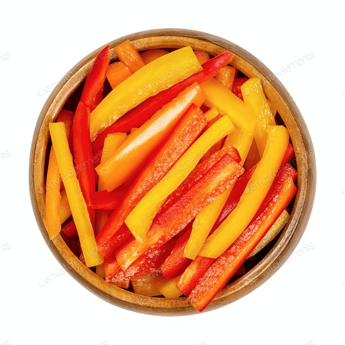 A heap of sliced bell peppers, sweet peppers, capsicum in a wooden bowl