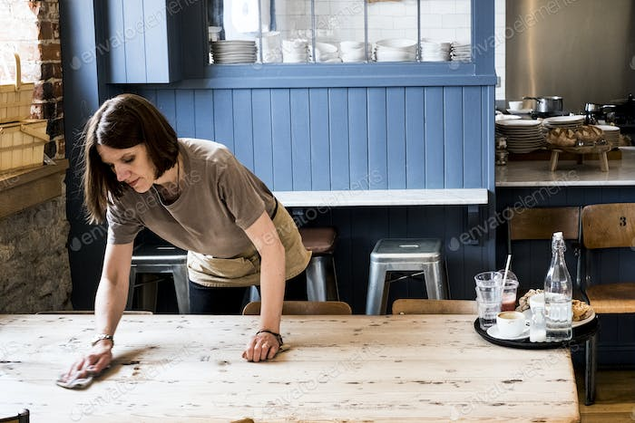 A female waitress clearing a table and wiping it in a cafe.