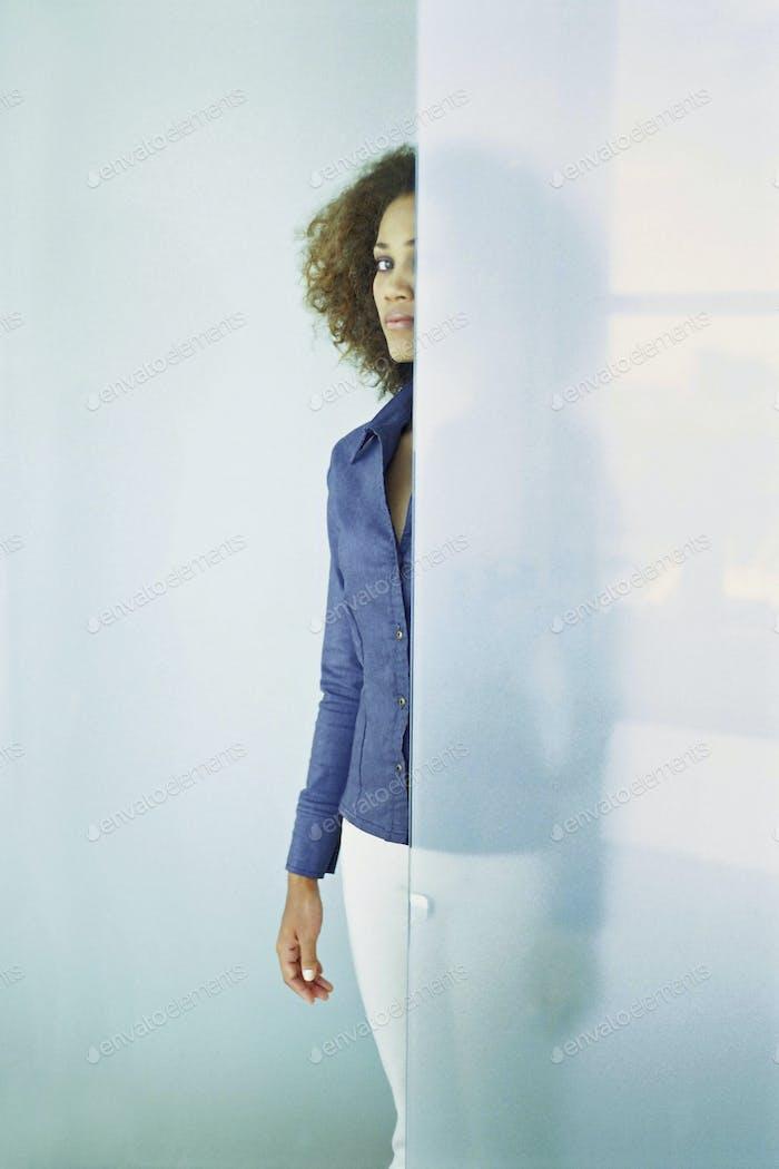 Black businesswoman standing behind glass wall
