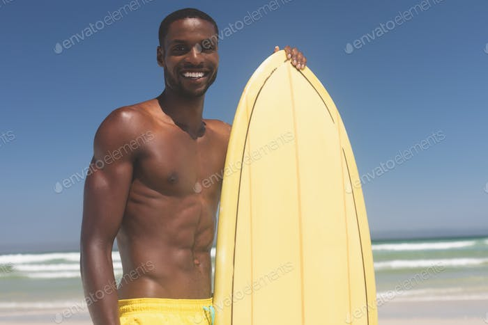 Male surfer with a surfboard standing on a beach on a sunny day