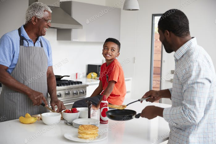 Multi Generation Male Family In Kitchen At Home Making Pancakes Together