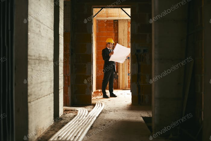 Architect Standing In House Under Construction With Plans