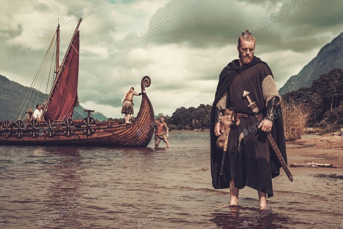 Viking warrior with sword standing near Drakkar on the seashore