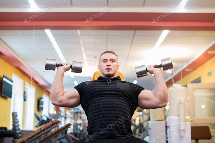 Handsome powerful athletic man doing barbell shoulder press exercise. Strong bodybuilder with