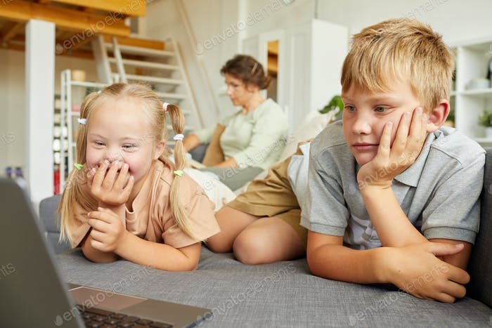 Girl with Down Syndrome Watching Cartoons with Brother