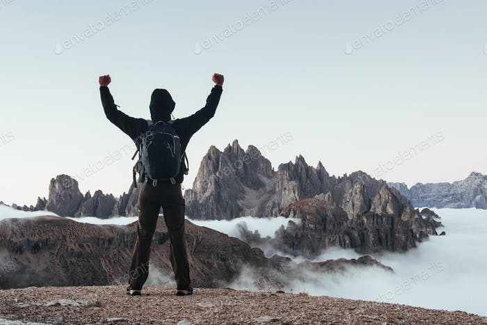New achievement. Touristic man raised his hands up on the beautiful daylight mountains full of fog