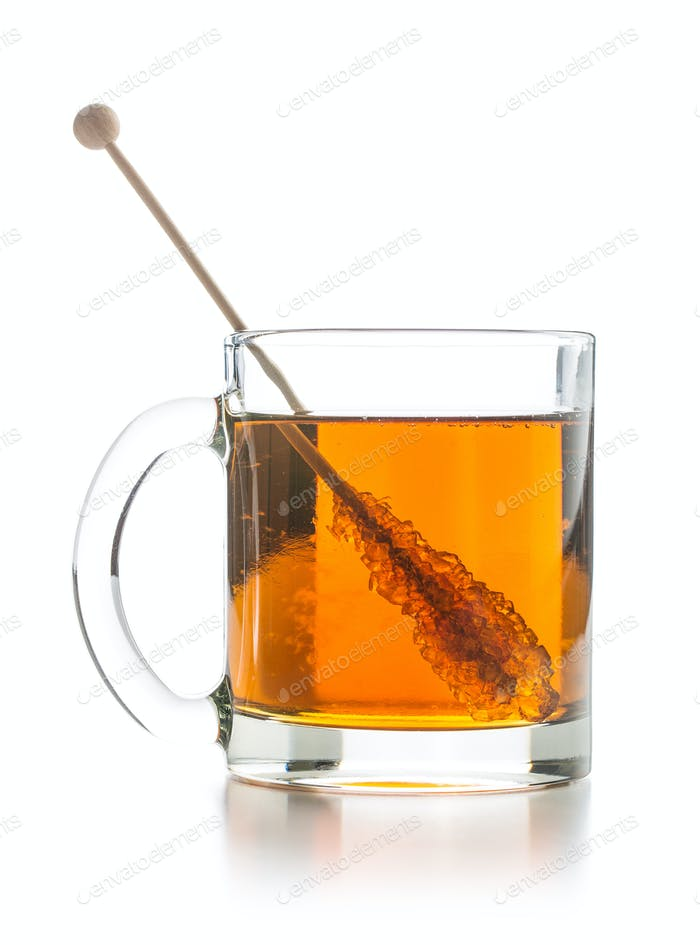 Tea cup with sugar crystal on wooden stick.