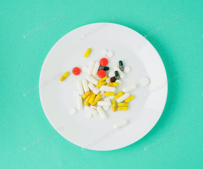 handful of scattered medicines, pills and tablets on white plate on blue background