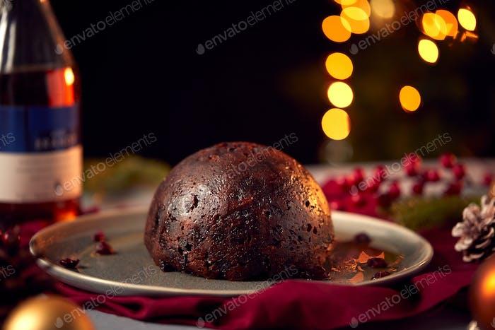 Brandy Soaked Christmas Pudding On Table Set For Festive Christmas Meal