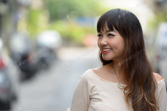 Portrait of young beautiful Asian businesswoman in the city