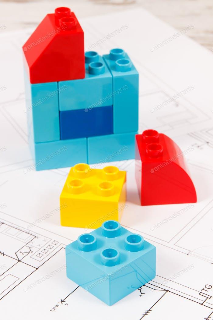Coloridos bloques de juguete y dibujos de construcción de la casa. Concepto de construcción, compra o alquiler de viviendas