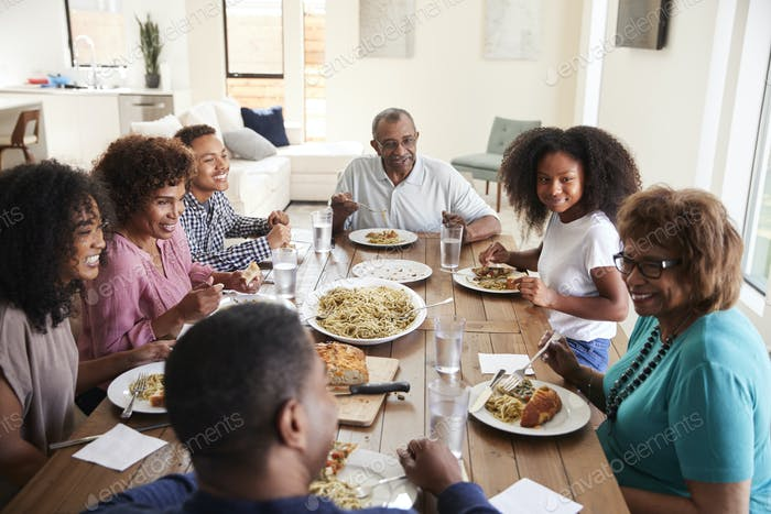 Three generation black family sitting at the table talking and eating dinner together, close up