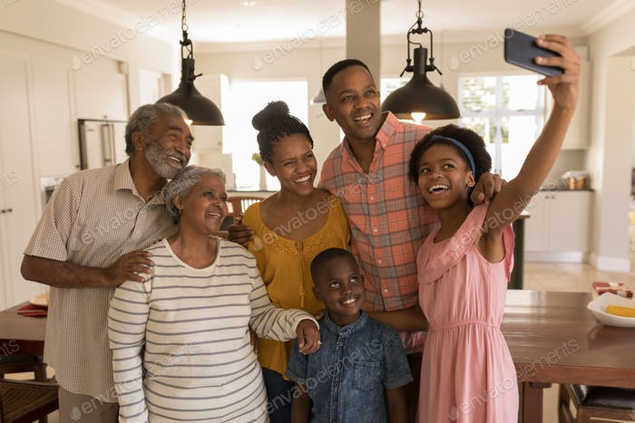 Multi-generation family taking selfie with mobile phone at home