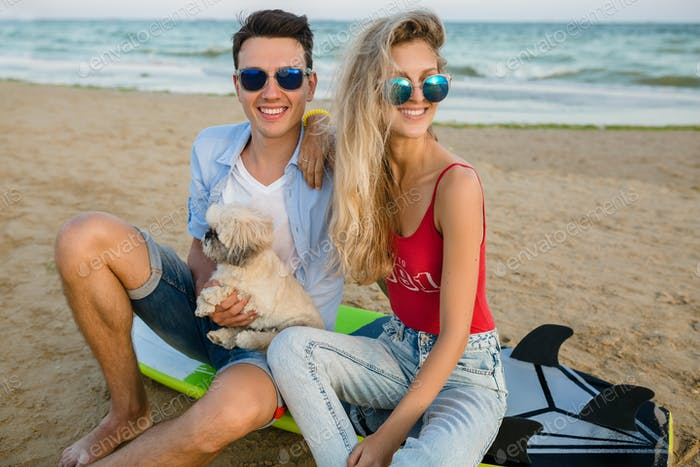 young smiling couple having fun on beach sitting on sand with surf boards playing with dog