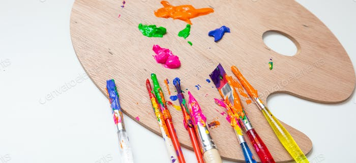 Paintbrushes, colorful paints and wood palette on white color background