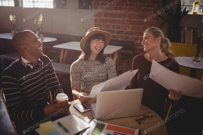 Cheerful creative team sitting with papers and laptop at table