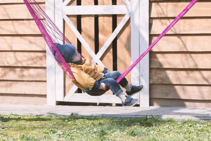 Small kid relaxing on pink hammock in spring garden