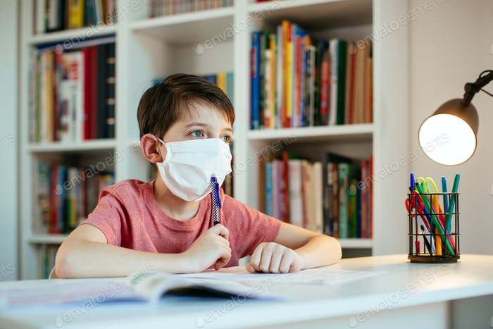 Child wearing face mask self-studying at home during coronavirus
