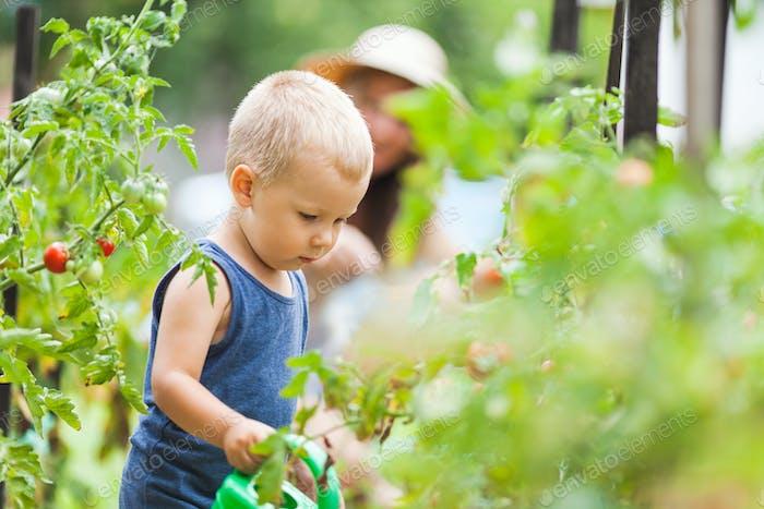 lindo niño ayuda mamá en el jardín